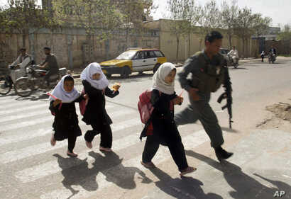 FILE - An Afghan policeman walks with school girls across the road in Herat, west of Kabul, Afghanistan, March 16, 2010.