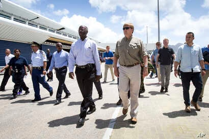 This photo provided by the Dutch Defense Ministry shows Dutch King Willem-Alexander, center right, visiting after the passing of Hurricane Irma, in Dutch Caribbean St. Maarten, Sept. 11, 2017.