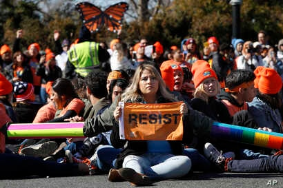 "A woman holds up a sign that says, ""resist,"" as supporters of the Deferred Action for Childhood Arrivals (DACA) block an intersection near the U.S. Capitol  in support of DACA recipients, March 5, 2018, on Capitol Hill in Washington."