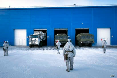 In this photo taken on April 3, 2019, a Russian military's Pansyr-S1 air defense system, left, and two Bastion missile launchers, right, leave a garage during a military drill on the Kotelny Island.