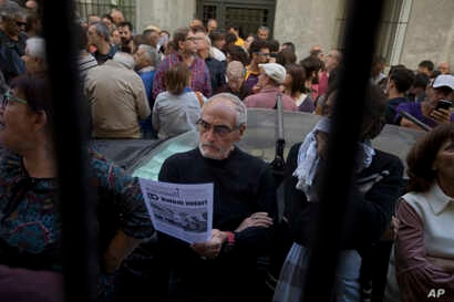 A man stands in the street reading a pamphlet urging people to vote during an event to support the Catalonia independence referendum in Madrid, Spain, Sept. 17, 2017.