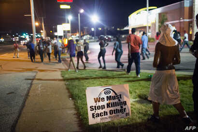 Demonstrators, marking the one-year anniversary of the shooting of Michael Brown, protest along West Florrisant Street on August 11, 2015 in Ferguson, Missouri.