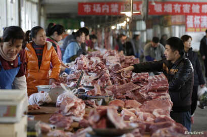 Meat stalls are seen at a market in Beijing, China, March 25, 2016. An exodus of small pig farmers in China is prolonging an industry downturn that will see the world's biggest pork producer and consumer challenge Japan as the top importer in 2016 fo...
