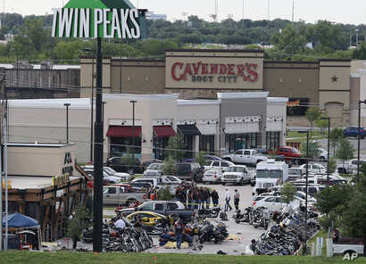 FILE - Authorities investigate a shooting in the parking lot of Twin Peaks restaurant in Waco, Texas. An indictment announced by the U.S. Attorney's Office in San Antonio accuses three Bandidos leaders of sanctioning a three-year fight that included ...