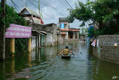 A man paddles a boat through flooded village in Chuong My district, Hanoi, Vietnam, July 31, 2018.