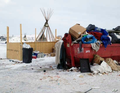 Trash is piled in and around a dumpster at an encampment set up near Cannon Ball, North Dakota., Feb. 8, 2017, for opponents against the construction of the Dakota Access pipeline.