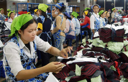 FILE - Cambodian garment workers work inside a factory in Phnom Penh.