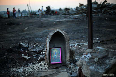 FILE - A religious image rests front of debris of an immigrant's shack after an accidental fire in Santiago, Chile, Dec. 14, 2016.