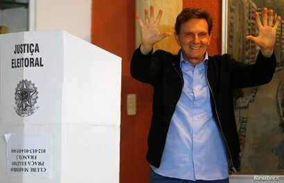 Senator Marcelo Crivella, candidate for Rio de Janeiro mayor, gestures to photographers after voting during the municipal elections at a polling station in Rio de Janeiro, Brazil, Oct. 30, 2016.