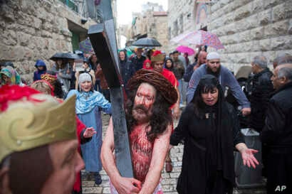 An actor dressed as Jesus Christ carries a cross as he reenacts the crucifixion walk along the Via Dolorosa towards the Church of the Holy Sepulchre, traditionally believed by many to be the site of the crucifixion of Jesus Christ, during the Good Fr...