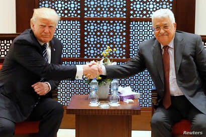 U.S. President Donald Trump (L) and Palestinian President Mahmoud Abbas shake hands before beginning their meeting at the Presidential Palace in the West Bank city of Bethlehem, May 23, 2017.