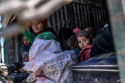 Children sit together in a truck as a convoy of vehicles led by U.S.-backed Syrian Democratic Forces (SDF) transports fighters believed to be surrendering members of Islamic State (IS) group and their families out of IS's last holdout of Baghuz, Syri...