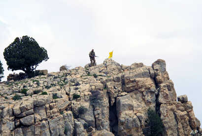 FILE - A Hezbollah fighter stands on a hill next to the group's yellow flag in the fields of Assal al-Ward, Syria, May 9, 2015. Experts say Iran's sending Afghan refugees to fight on the Syrian front, alongside Hezbollah and Iranian forces, has long-...