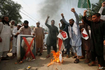 Pakistani protesters shout slogans to condemn a cartoon contest by Dutch parliamentarian, in Peshawar, Pakistan, Aug. 17, 2018.