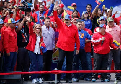President Nicolas Maduro and first lady Cilia Flores greet supporters as they arrive at a rally in Caracas, Venezuela, Feb. 2, 2019.