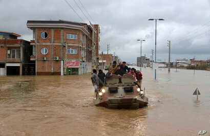 Military vehicles rescue people after flash flooding around the northern city of Aq Qala in Golestan province, Iran, March 25, 2019.