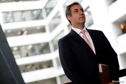 FILE - Michael Cohen, President Donald Trump's personal attorney, looks on as his attorney (not pictured) delivers a statement to reporters after meeting with Senate Intelligence Committee staff on Capitol Hill in Washington, Sept. 19, 2017.