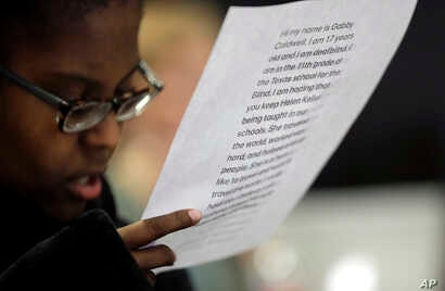 Gabrielle Caldwell, who is partially deaf and blind, looks over her notes before speaking to the Texas school board on history curriculum, Nov. 13, 2018, in Austin, Texas. The Republican-controlled board heard from activists and academics who were de...