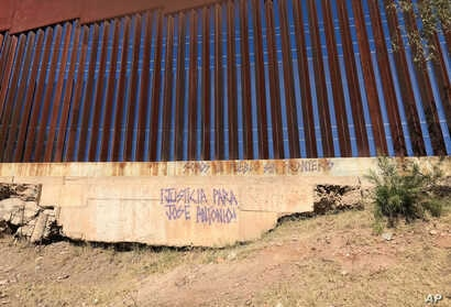 FILE - An inscription asking for justice for Jose Antonio Elena Rodriguez, 16, who was shot and killed on a street in Nogales, Sonora, Mexico, is displayed at the border wall where he was killed, Dec. 4, 2017.