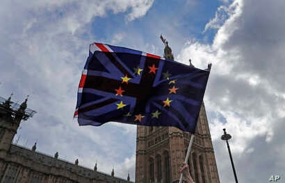 A pro-EU protestor waves flags opposite the House of Parliament in London, Apr. 4, 2019.