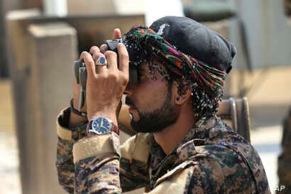 Abdullah, an Arab fighter with U.S.-backed Syrian Democratic Forces (SDF), looks through his binocular to an airstrike that hit an Islamic state militant group position, in Raqqa, northeast Syria, July 22, 2017.