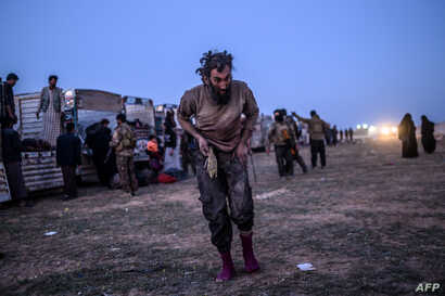 A man suspected of belonging to the Islamic State group walks past members of the Kurdish-led Syrian Democratic Forces just after leaving IS' last holdout of Baghuz, in the eastern Syrian province of Deir Ezzor on March 4, 2019.