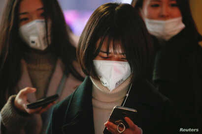 Women wearing face masks wait for the bus on an extremely polluted day with red alert issued, in Langfang, Hebei province, China, Dec. 19, 2016.