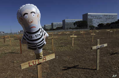 A doll representing Brazil's President Luiz Inacio Lula da Silva wearing prison clothes stands on a cross with his name in Brasilia, Brazil, Sunday, Aug. 27, 2017. Demonstrators placed crosses representing the death of corrupt politicians.