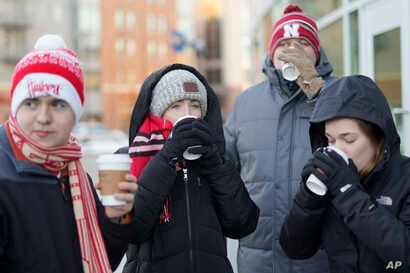 University of Nebraska students sip complementary hot chocolate as they wait in freezing temperatures to be admitted to Pinnacle Bank Arena for an NCAA college basketball game against Wisconsin, in Lincoln, Neb., Jan. 29, 2019.
