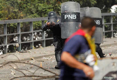 A police officer fires rubber bullets at demonstrators during a protest against Venezuelan President Nicolas Maduro's government, in Caracas, Venezuela Jan. 23, 2019.