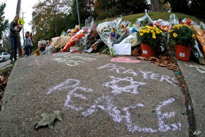 A mother and her child arrive to place flowers at a spontaneous memorial of flowers and sidewalk writing a block from the Tree of Life Synagogue, Oct. 29, 2018.