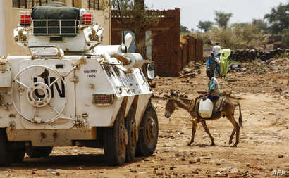A Sudanese boy rides a donkey past a UN-African Union mission in Darfur (UNAMID) armoured vehicle in the war-torn town of Golo in the thickly forested mountainous area of Jebel Marra in central Darfur.