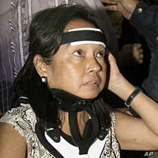 Former Philippine President Gloria Macapagal Arroyo is seen with a neck brace as she arrives on a wheelchair for a flight to Hong Kong at the Ninoy Aquino International Airport in Paranaque, Manila November 15, 2011