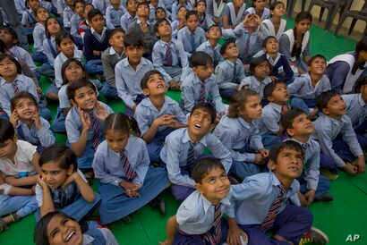 School children look at a drone camera during the inauguration ceremony of a water filtration tower at their school in Nai Basti Village, near New Delhi, India, March 22, 2017.