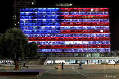 People walk by as the municipality building in Tel Aviv is lighted in the colors of the American flag in solidarity with the victims of the Pittsburgh, Pa., synagogue attack, Oct. 27, 2018.