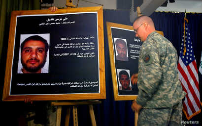 FILE - A U.S. soldier shows a picture of  Ali Musa Daqduq during a news conference at the heavily fortified Green Zone area in Baghdad, July 2, 2007.
