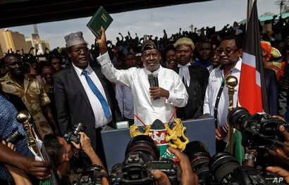 "FILE - Opposition leader Raila Odinga (C) accompanied by lawyers Miguna Miguna (C-L), Tom ""T.J."" Kajwang, (C-R) and politician James Orengo (R) holds a bible aloft after swearing an oath during a mock ""swearing-in"" ceremony at Uhuru Park in downtown ..."