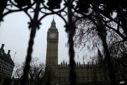 FILE - The Houses of Parliament and Elizabeth Tower, containing the bell know as Big Ben, are seen through a perimeter fence in London, Feb. 8, 2017. Lawmakers on the House of Commons' international development committee released a report Tuesday war...