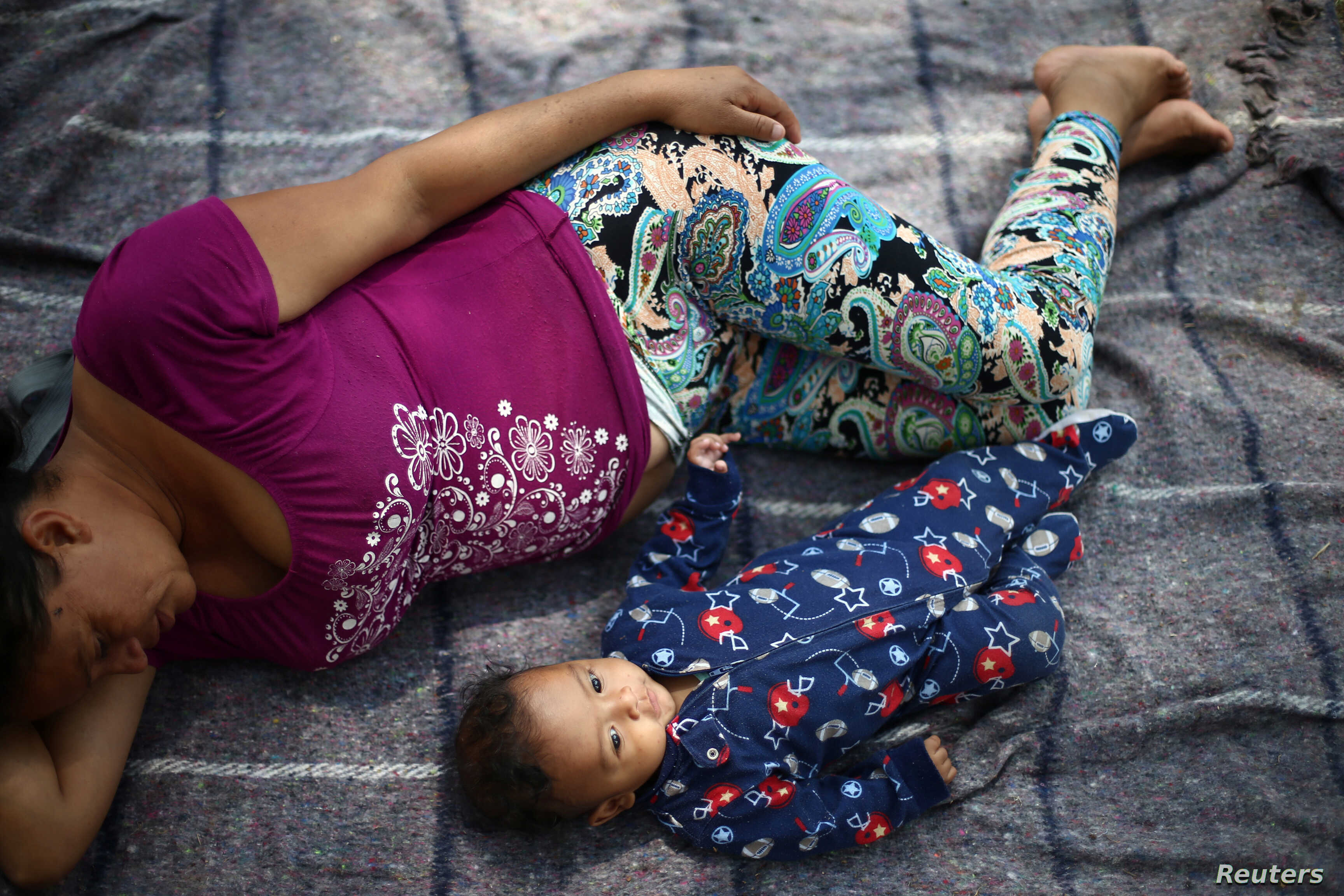 Aide and her baby son Clesner from Guatemala, rest after arriving with fellow Central American migrants, who are moving in a caravan through Mexico toward the U.S. border, at a shelter set up by the Catholic church, in Puebla, Mexico April 6, 2018.