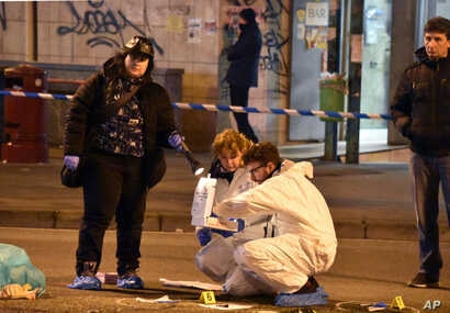 Italian forensic police inspect an area after a shootout between police and a man near a train station in Milan's Sesto San Giovanni neighborhood, Italy, Dec. 23, 2016.