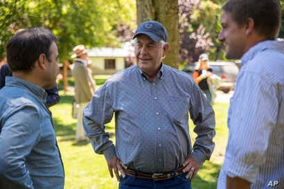U.S. Secretary of State Rex Tillerson, center, meets with locals at a horse riding operation in Bariloche, Argentina,  Feb. 3, 2018.