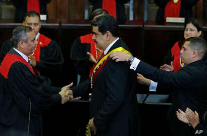 Venezuela's President Nicolas Maduro, center, shakes hands with Supreme Court President Maikel Moreno as his presidential sash is adjusted, after he took the oath of office in Caracas, Jan. 10, 2019. Maduro's second, six-year term starts amid interna...