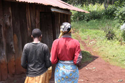 A mother walks beside her mentally disabled 14-year-old daughter who was raped by a neighbor in Kabazi, Kenya, August 24, 2010.
