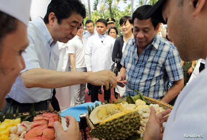 Philippine President Rodrigo Duterte and Japan's Prime Minister Shinzo Abe (left) try durian fruit after attending various events at the Waterfront Hotel in Davao City, southern Philippines, Jan. 13, 2017.