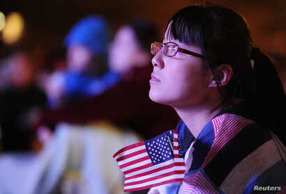 Kim Li, a junior at Denver University, watches the first 2012 U.S. presidential debate between U.S. President Barack Obama and Republican presidential nominee Mitt Romney on an outdoor screen at Denver University in Denver, Colorado October 3, 2012. ...