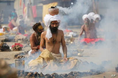 """Hindu holy men burn dried cow dung cakes as they perform a ritual at Sangam, confluence of rivers Ganges and Yamuna on """"Basant Panchami"""" day at the annual traditional fair of Magh Mela in Allahabad, India, Monday, Jan. 22, 2018."""