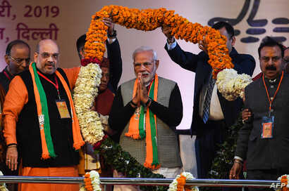 Indian Prime Minister Narendra Modi, center, is garlanded by BJP leaders on the first day of the two-day Bharatiya Janata Party national convention in New Delhi, Jan. 11, 2019.