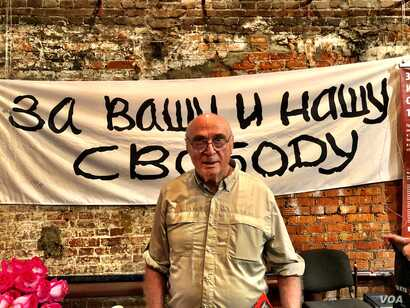 Pavel Litvinov at a Moscow exhibit to mark the 50th anniversary of his demonstration against the Soviet Union's invasion of Czechoslovakia in 1968.  Behind him is a reproduction of the banner he and 7 other protesters unfurled on Red Square.  It read...