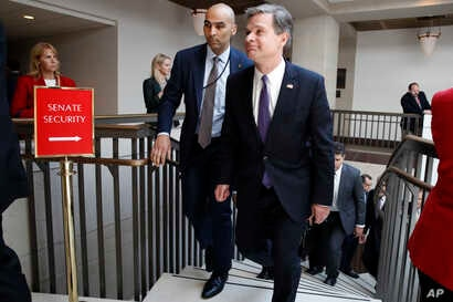 FBI Director Christopher Wray, right, leaves a classified briefing about the federal investigation into President Donald Trump's 2016 campaign, on Capitol Hill in Washington, May 24, 2018.