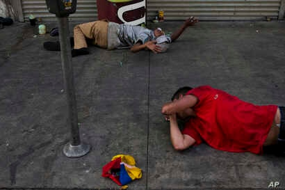 Lying on a urine-stained sidewalk, two homeless drug addicts hallucinate in Los Angeles' Skid Row area, home to the nation's largest concentration of homeless people, Sept. 1, 2017.